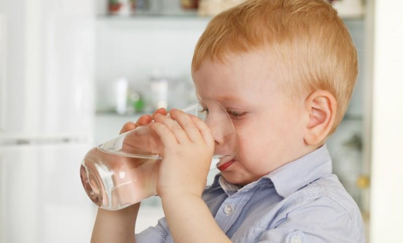 Ребенок запивает таблетку водой